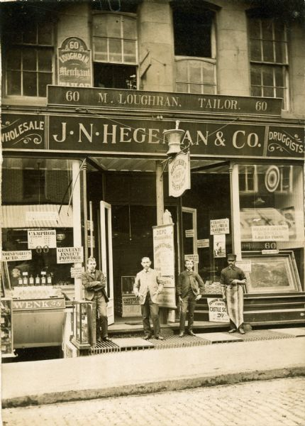 Exterior view of the J.N. Hegeman Drugstore at 60 Fulton Avenue. Left to right: a clerk, J.W. Ferris, an errand boy, William O'Bry, and a porter.