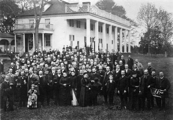 Slightly elevated view of the members of the United States Pharmacopeial Convention and their families standing for a portrait at Mount Vernon.