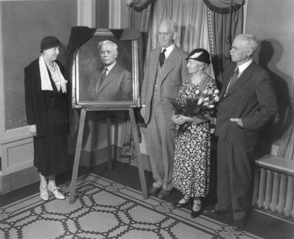 View of a ceremony in which an oil portrait of University of Wisconsin pharmacist Edward Kremers was unveiled. Pictured are (right to left): Nellie Wakeman, Dean George Sellery, and Mrs. and Mr. Kremers.