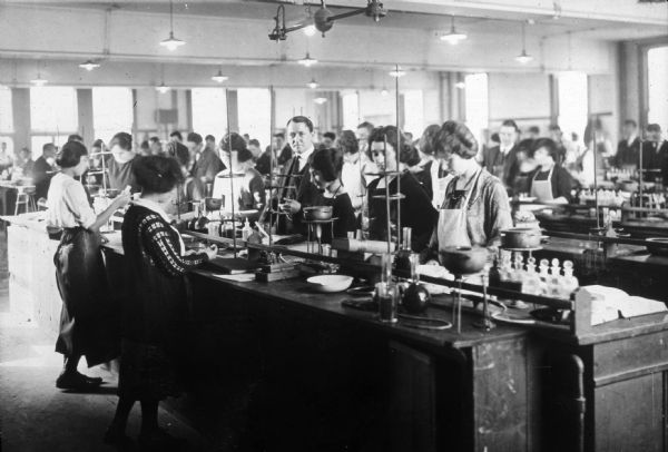 A professor checks the progress of several female students in a pharmaceutical laboratory course.