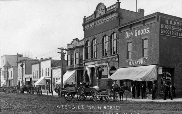 View of the west side of Main Street.  Stores pictured (right to left):  Kypke's Dry Goods store, Heimstreet's Drugstore, and a saloon.