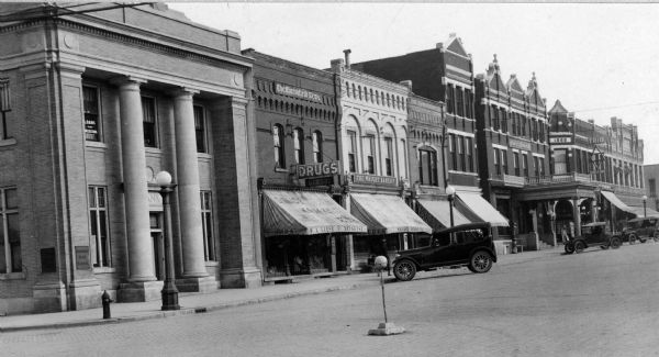 View of cars parked outside of several downtown businesses. Pictured from the left are a bank, Liese Drugstore, the Wright Bakery, two unidentified awnings, the Hotel Blodgett, and the Trio Theatre.