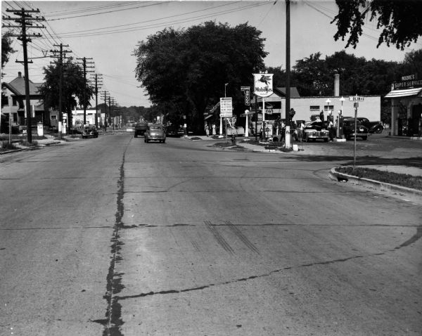 A view down Park Street at Olin Avenue. On the corner of Olin is Moore's Super Service Mobil Station and McCranner Drugs.