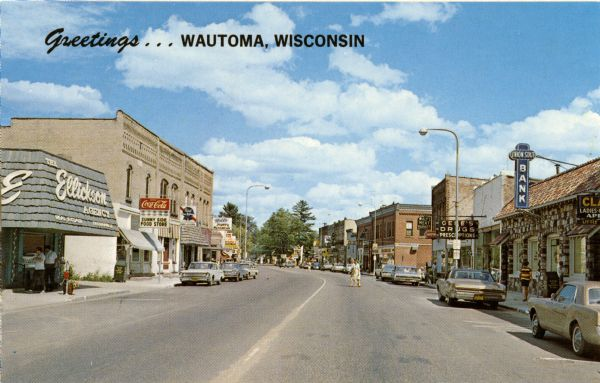 View of businesses in the Main Street area of Wautoma. Some storefronts featured are, on the right, Ellickson Agency, Sunny Side Food Store, a bar, a mens' wear store, and, on the left, Union State Bank and Gene's Drugs.