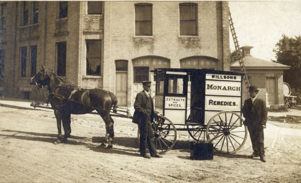 "Two salesmen stand beside one of the Willson's Monarch Remedies horse-drawn wagons. Willson's sold patent medicines, spices, extracts, flavorings, and ""toilet articles""."