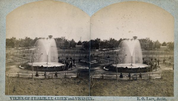 "Stereograph of the Artesian Well near the intersection of Wisconsin and Minnesota (later renamed Wacouta) Streets. The following is printed on the back of the photograph: ""The Greatest Artesian Well in America. The Largest Flow in the World, of the Same Size Bore, with One Exception. This well was completed in February 1876, bore 5 5/8 inches; pipe projects 10 feet above the ground the water falling into a basin 30 feet in diameter. A movable cap on top of the pipe obstructing the upward flow, and the water is forced outward and upward in all directions, by a pressure of 20,000 pounds. Depth 960 feet or 970 from top of pipe. Temperature 56 F. Water flowed to top of pipe at a depth of 268 feet. Discharge per minute 603 9-10 gallons or nearly 30,000 bbls. Water will rise in a pipe 60 feet above ground or 100 feet above the Mississippi river. The whole distance that the water will rise is 1,020 feet above the bottom of the well. The pipe goes down 147 feet through sand and gravel to rock, first lime-rock 2 feet, shale 107 feet, sand rock 118 feet, sandy shale 90 feet, red and yellow ocher 6 feet, sandy shale 25 feet, sand-rock 4 feet (here brine begins to flow), sandy shale 71 feet, red, white and yellow sandstone in alternate layers, 355 feet, conglomerate of water-worn quartz-pebbles 35 feet, to bottom of well; which is 327 1/2 feet below the level of the ocean. The water from this well is found to possess rare medicinal properties, and has cured many diseases of the bladder and kidney, Rheumatism, Dispepsia, St. Vitus dance, chronic female complaints, and has infused new life and vigor into the aged and debilitated."""