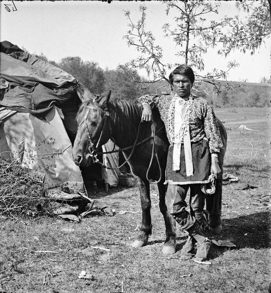"""Second Boy and Pony Indian."" Ho-Chunk man standing with legs crossed, leaning on his pony. A typical dwelling (chipoteke) is in the background."