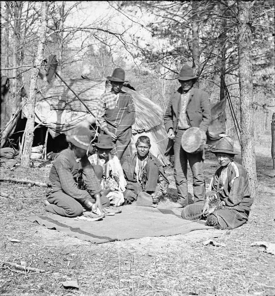 Six Ho-Chunk men are standing and kneeling around a blanket playing Wah-koo-chad-ah (Moccasin), a favorite game. A typical dwelling (chipoteke) is in the background.