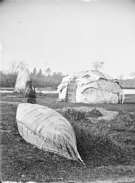 View towards a Ho-Chunk Indian standing behind a beached canoe. In the background are two typical dwellings (a chipoteke and a tepee or tipi) and beyond is a body of water.