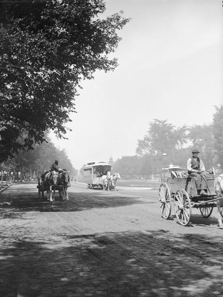 View looking up Grand Avenue from 9th Street toward two horse-drawn wagons and a horse-drawn streetcar on the tree-lined street. The wagon on the right is carrying firewood.