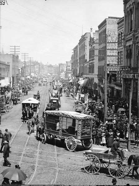 Circus parade at the corner of West Water and Grand Avenue. Crowds on the sidewalk and in horse-drawn vehicles are watching horse-drawn cages and other vehicles with flags.