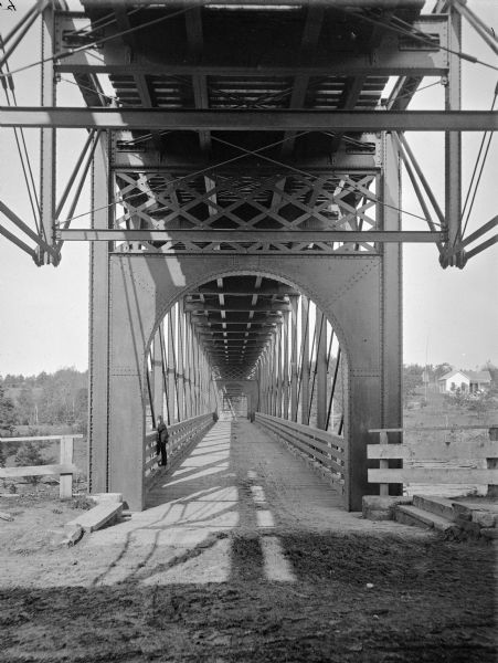 Interior of railroad bridge, with walkway below. There is a man standing on the left at the railing of the walkway.