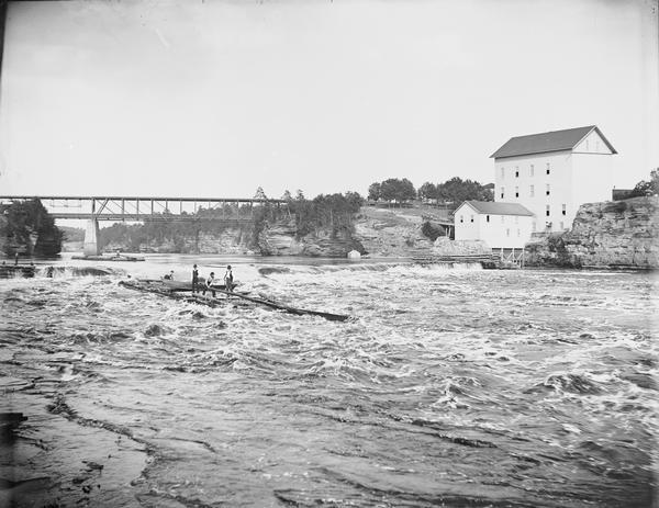 View across water of several men steering a lumber raft over the dam at Munger's Mill. A second raft is in the background, in front of railroad bridge.