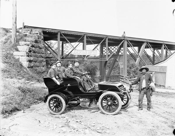 A.C. Bennett posing in a car, which is parked in front of Kilbourn Bridge, with three other men. A man is standing at the front of the car and another is sitting on the bridge.