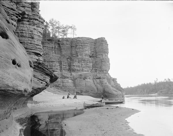 At the foot of High Rock (north face). Two women sit on shore. Third woman sits on canoe at edge of shore.