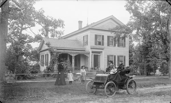 The H.H. Bennett House, Kilbourn, with members of the family posing in front of the house and in a 1901 Winton automobile. Ashley Bennett, the son of the famous photographer, is tentatively identified as the driver of the car which is so early that has a tiller rather than a steering wheel. Like his father, Ashley had a talent for tinkering and even experimented with building his own airplane. Ashley was in the automobile business in Minneapolis.