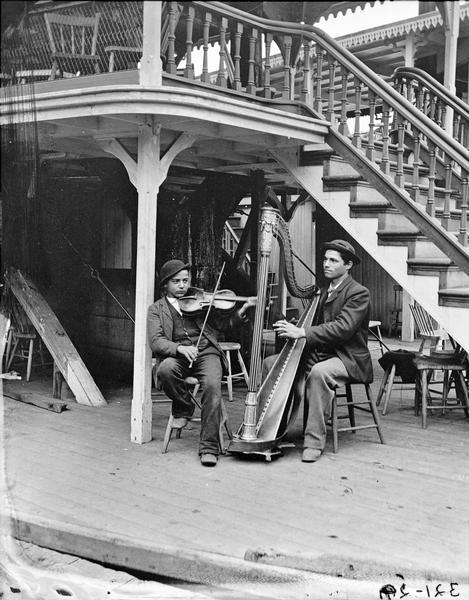 "Harpist and violinist posed on the steamboat ""New Dell Queen."""