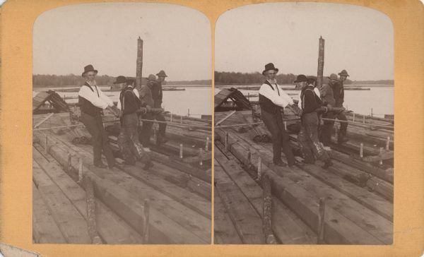 Stereograph view of five men on a raft working a Spanish windlass.