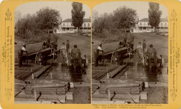 Stereograph of men unloading lumber off a raft. A man at the left loads lumber onto a horse-drawn wagon while a man in an apron holds the horses. There is a boy standing in the center. On the right a man loads lumber onto a second wagon. The rafts loaded with lumber are in the foreground. There is a large building on a hill in the background.