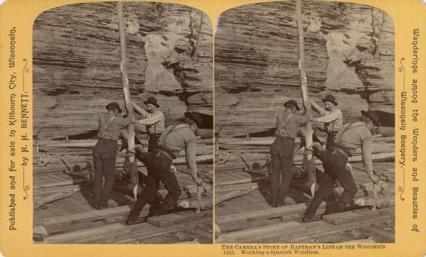 Stereograph of four men on a raft working a Spanish windlass. The raft is in front of a rock wall.