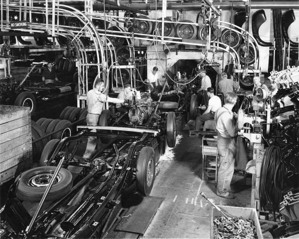 General Motors chassis assembly. Men are working among the machinery.