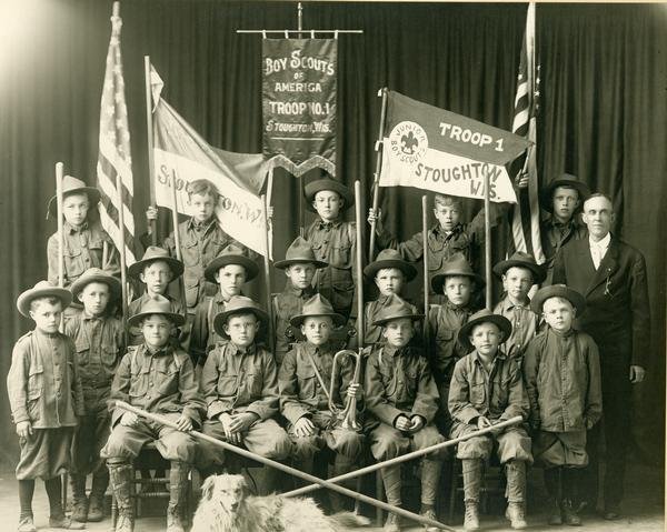 Stoughton, Wisconsin Boy Scouts of America Troop No. 1 group portrait with a dog in the front of the group. One of the members is holding a trumpet.