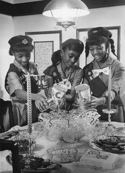 African American junior Girl Scouts pouring fruit juice into a punch bowl as they prepare to entertain their parents.