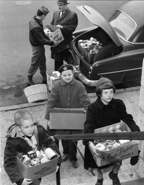 Elevated view of a Cub Scout, Girl Scout, and Brownie Scout standing on the sidewalk bringing boxes of food to St. Vincent de Paul to be distributed to recently arrived Hungarian refugees.