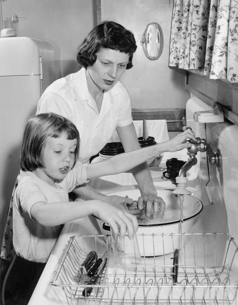 Mother and daughter washing dishes together.