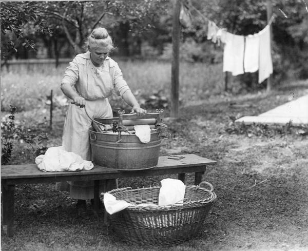 Woman washing clothes outdoors with a washtub, washboard, wringer, clothespins and clothesline.
