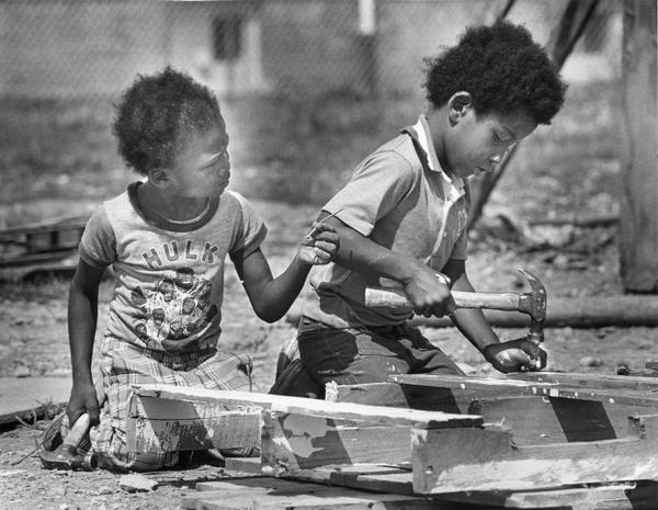 Two young boys using hammers and nails.