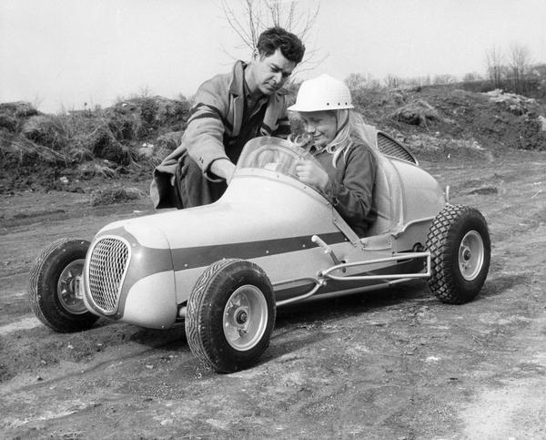 Father demonstrates controls of a mini-race car as his daughter sits in the car.