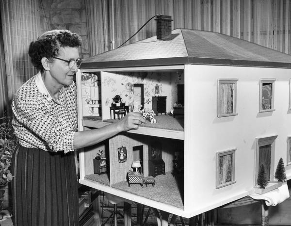 Woman makes a small adjustment to an interior room in a dollhouse.