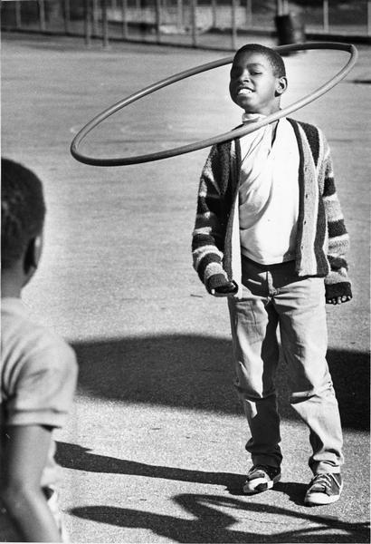 "A boy is twirling a ""hula-hoop"" around his neck while another child is watching from the left foreground."