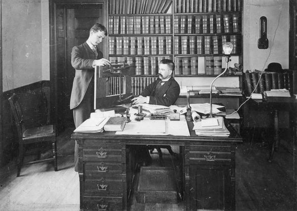 Patent attorney Charles L. Goss (seated), with clerk Arthur Muerless in the law offices of Winkler, Flanders, Smith, Bottum, & Vilas.
