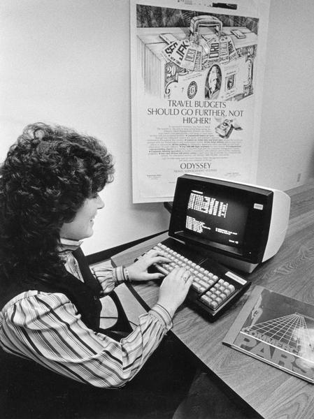 A woman uses an early commercial computer network that allows travel agents to book their own flights without the use of a telephone.