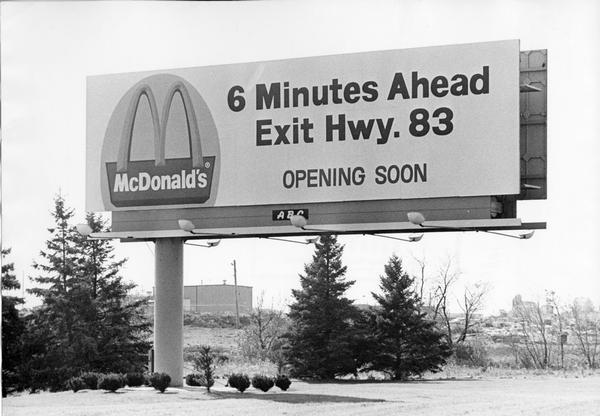 A billboard advertising the opening of a particular McDonald's restaurant. Express highways promoted the emergence of large signs that could be read at a distance by motorists traveling at high speed.