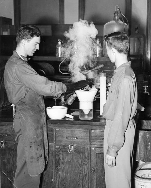 Chemistry experiment by two men being conducted with steam rising from equipment.