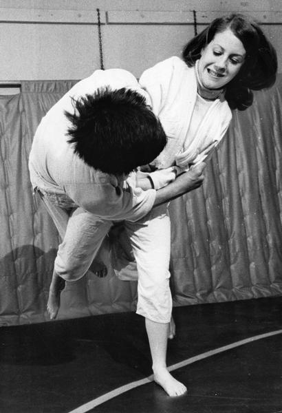 Woman judo student taking down a male opponent in practice for judo tournament.