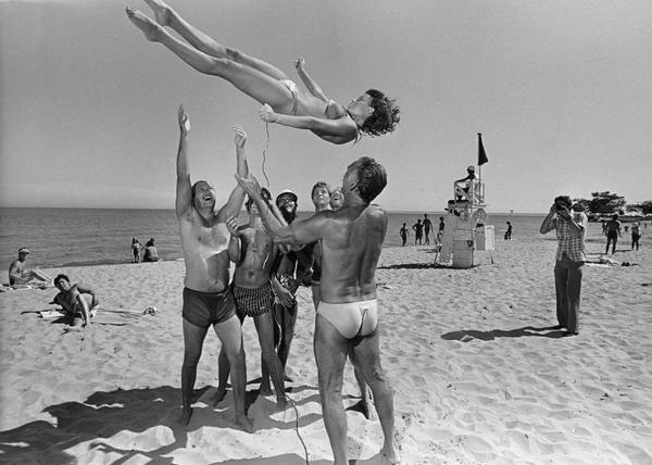 A bikini-clad woman snaps a self-portrait with a long cable release attached to a camera as she is tossed into the air by a group of men on the beach. Other people on the beach are watching and taking snapshots, and there is a lifeguard on a lifeguard station in the background.