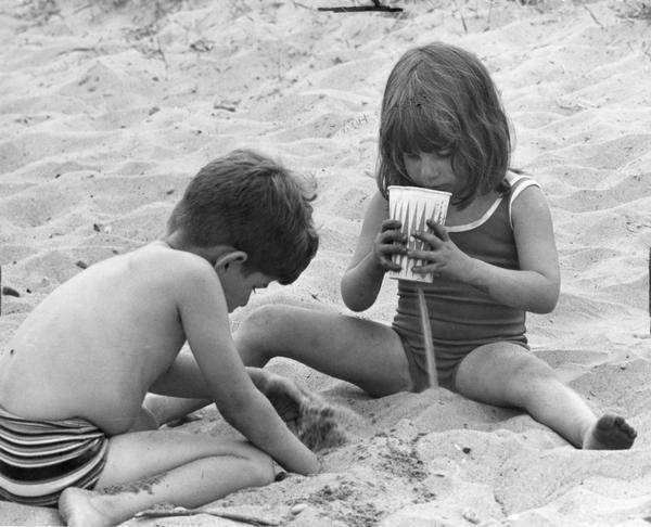 A boy and girl play in the sand at the beach.