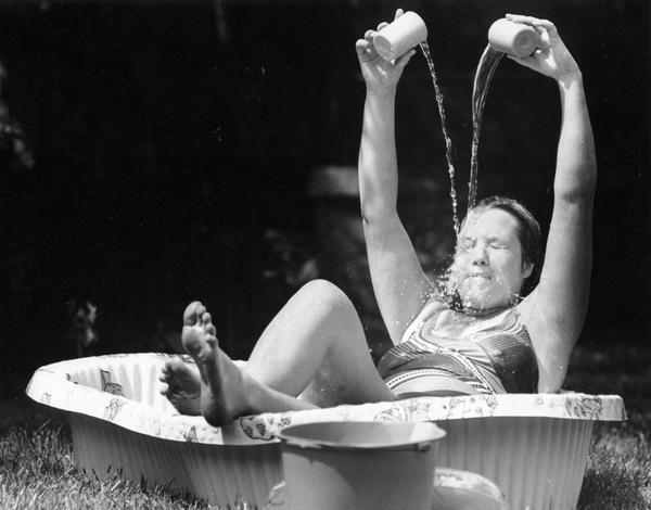 Woman stays cool by sitting in a small plastic pool while pouring cups of water on her head.