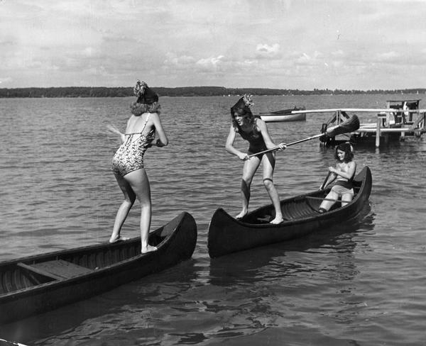 Two women try to knock each other off of their canoes while standing and swinging brooms at each other.
