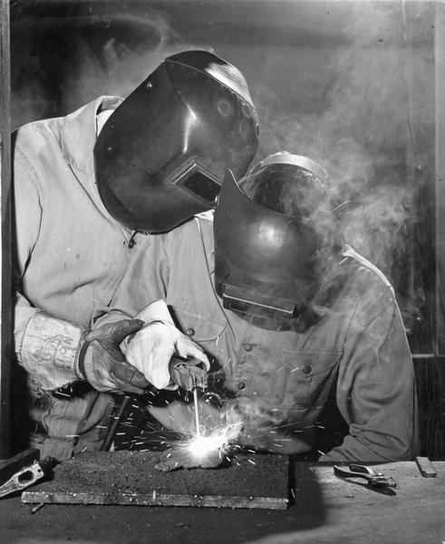Two students welding at the University of Wisconsin Agricultural Short Course.