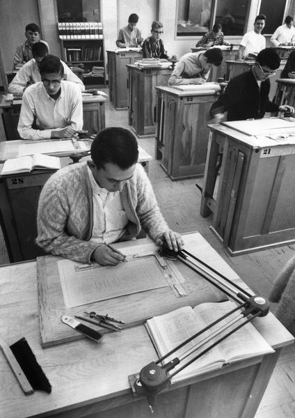High school boys in industrial drafting class using drafting machines and compasses.