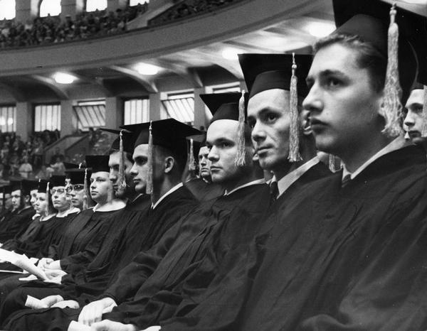 Graduates in caps and gowns attend the graduation ceremony.