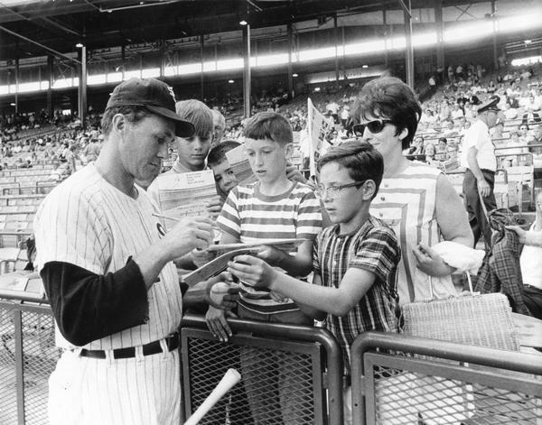 Chicago White Sox pitcher, Don McMahon, signs autographs for fans before a game.