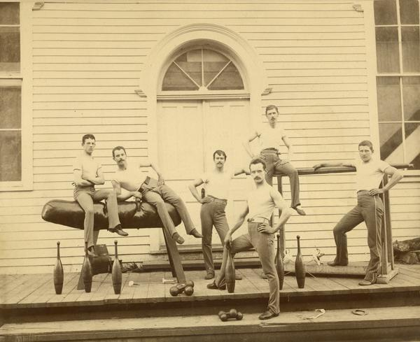 A male gymnastics team posing in front of a building.