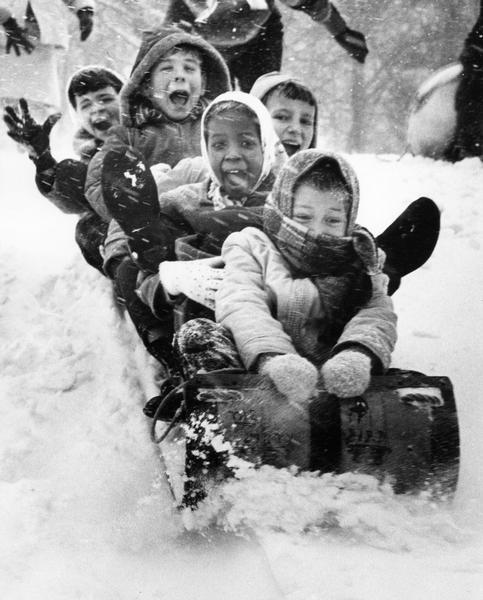A winter scene with excited children on a toboggan.