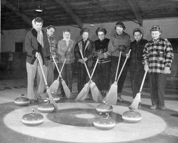 A female curling team poses with their brooms and stones for a portrait.